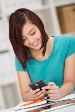 Pretty young Asian student reading a text message
