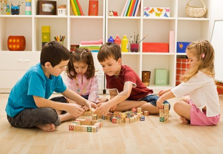 Photo for Children playing with blocks on the floor - focus on the boy's face - Royalty Free Image