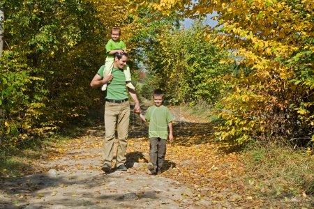 Photo pour Père et ses deux enfants marchant sur le chemin pendant l'automne - image libre de droit
