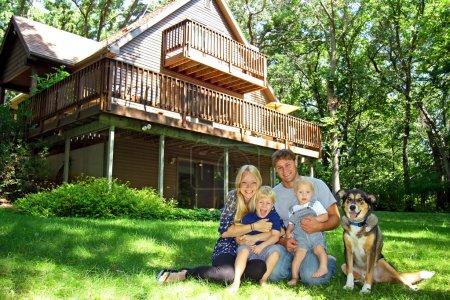 Photo pour Une famille jeune, séduisante et heureuse de quatre personnes, mère, père, bébé et jeune enfant, est assise dehors avec son chien devant une cabane magnifique par une journée ensoleillée d'été - image libre de droit