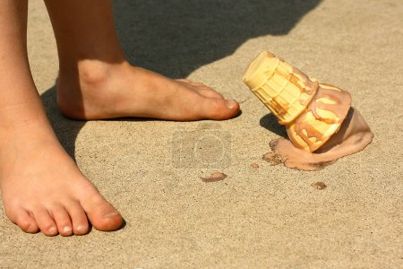 Photo for Child Drops Ice Cream Cone by Feet - Royalty Free Image