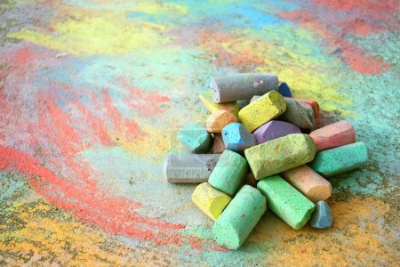 Photo for A collection of colorful sidewalk chalk is piled up on a rainbow drawing, outside on the pavement. - Royalty Free Image