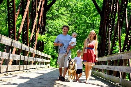 Foto de Una familia de cuatro personas cruzando un puente joven y atractiva. - Imagen libre de derechos