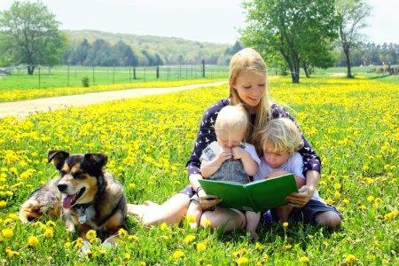 Photo pour Une jeune jolie mère lit un livre d'histoire à ses deux enfants assis dehors dans une prairie avec leur chien - image libre de droit