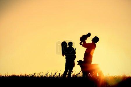 Photo pour Une silhouette d'une heureuse famille de quatre personnes, mère, père, bébé, enfant et leur chien devant un ciel de temporisation, avec une salle pour l'espace de copie ou de texte - image libre de droit