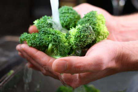 Photo for The hands of a man are holding fresh broccoli sprouts under running water, and washing them in the kitchen sink. - Royalty Free Image