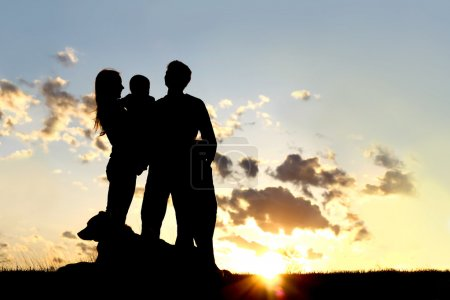 Photo for A sillhouette of a happy young family of four people, mother, father, child, and baby, stand outside in front of a sunset in the sky with their pet German Shepherd Dog. - Royalty Free Image