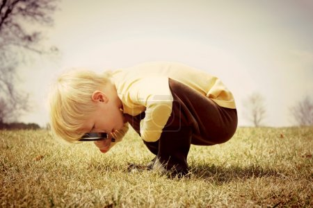 Photo for A young child is bending down looking in the grass, investigating something with a magnifying glass.  Vintage style color. - Royalty Free Image