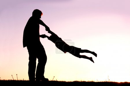 Photo pour Une silhouette d'un jeune père ludique de filature et de danser avec son petit enfant dehors au coucher du soleil sur une journée d'été. - image libre de droit