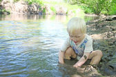 Young Child Sitting in the River During Summer