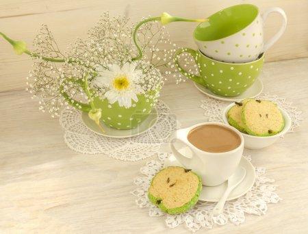 Photo pour Bouquet de fleurs blanches dans une tasse à pois verts, cacao au lait et biscuits en forme de pomme pour la fête des mères. Près de biscuits sucrés en forme de pommes - image libre de droit