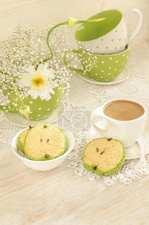 Photo pour Bouquet de fleurs blanches en tasse à pois verts, café tasse et biscuits en forme de pomme pour la fête des mères. Près de biscuits sucrés en forme de pommes - image libre de droit