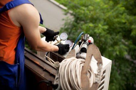 Photo pour Air conditionné maître prépare à installer le nouveau climatiseur. élimination des gaz provenant des tubes de fréon - image libre de droit