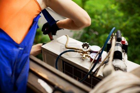 Photo pour Air conditionné maître prépare à installer le nouveau climatiseur. perçage du mur. - image libre de droit