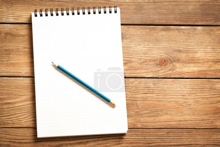 Photo for Blank notepad and a blue pencil on a wooden surface. - Royalty Free Image