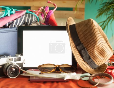 Photo for Digital tablet, airline ticket and other accessories ready to be packed for summer holiday. - Royalty Free Image