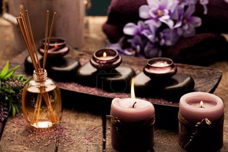 Photo pour Bougies, huile d'aromathérapie et pierres chaudes utilisées pour les traitements de spa. - image libre de droit