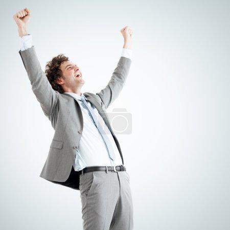 Photo pour Jeune homme d'affaires prospère levant les mains vers le haut en studio. - image libre de droit