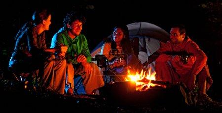 Photo pour Quatre amis assis autour du feu de camp dans la nuit et parler. - image libre de droit