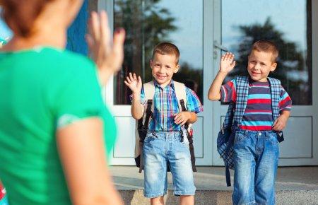 Photo pour Deux frères à leur mère en agitant leur premier jour à l'école. - image libre de droit