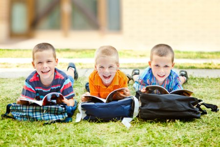 Photo for Three schoolboys lying on the ground and laughing while studying. - Royalty Free Image