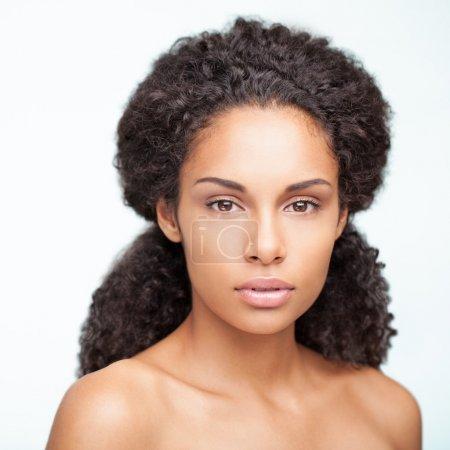 Photo pour Portrait d'une jeune femme africaine sensuelle pose contre un fond blanc. - image libre de droit