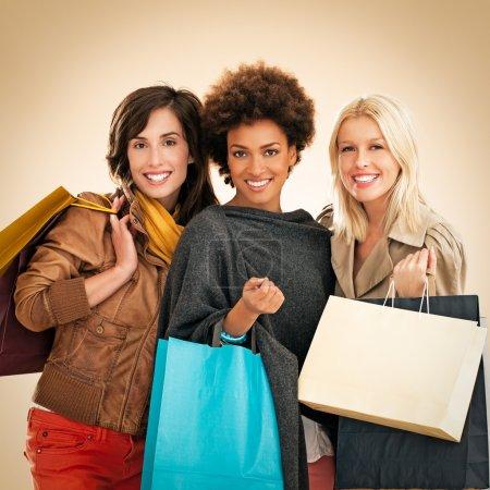 Photo pour Trois femmes différentes, portant sacs shoping. - image libre de droit
