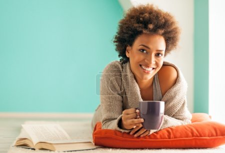 Photo for Beautiful young African woman enjoying a cup of coffee while relaxing at home. - Royalty Free Image