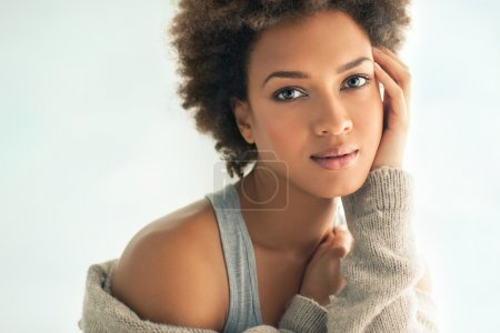 Photo for Beautiful young African woman gently touching her face. - Royalty Free Image