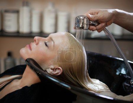 Photo pour Femme souriante, avoir les cheveux lavé dans le salon de coiffure. - image libre de droit