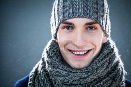 Photo pour Beau jeune homme vêtu d'un chapeau tricoté et un foulard. - image libre de droit