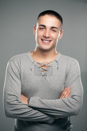 Photo for Portrait of a handsome smiling man standing with his arms crossed. - Royalty Free Image