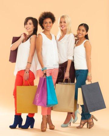 Photo pour Quatre femmes souriantes tenant des sacs à provisions . - image libre de droit