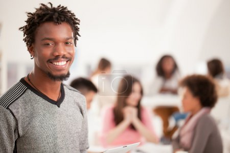 Portrait of a smiling African college student standing in front of his peers.