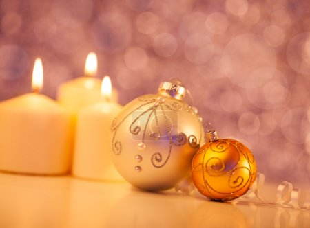 Photo for Christmas candles and ornaments in front of a glittering purple background. - Royalty Free Image