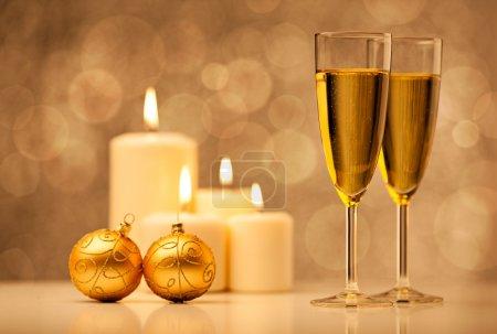 Foto de Velas de Navidad, adornos y dos copas de champagne frente a un brillante dorado fondo - Imagen libre de derechos