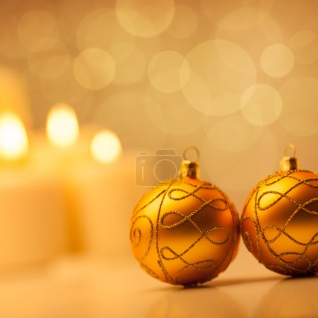Photo for Christmas candles and ornaments in front of a glittering golden background. - Royalty Free Image