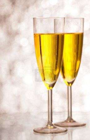 Photo pour Flûtes à champagne devant un fond argenté . - image libre de droit
