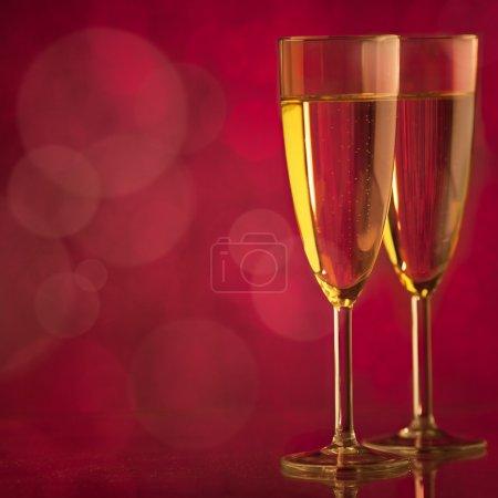 Photo pour Deux verres à champagne en gros plan devant un fond rouge scintillant . - image libre de droit