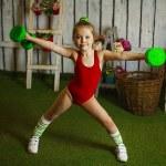 Little girl exercising  with dumbbells...