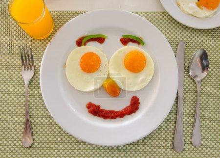 Photo pour Visage heureux petit déjeuner oeufs de friture. - image libre de droit