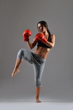 Photo pour Belle femme de fitness avec les gants de boxe rouges - image libre de droit