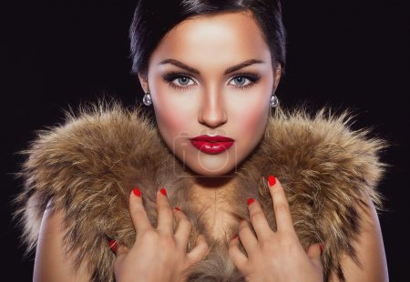 Photo for Portrait of a beautiful brunette with classic make up and red lips, holding her hands on fur - Royalty Free Image
