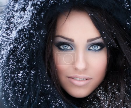Young woman in a snowy furry hood...