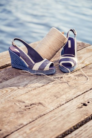 A ball of yarn around women sandals, shoes outdoors