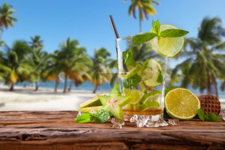 Photo for Mojito, lime drink on wood with blur beach background - Royalty Free Image