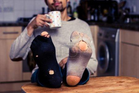 Homme avec des chaussettes usées prenant du café dans la cuisine