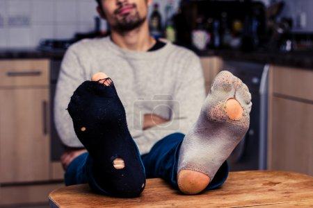 Homme avec des chaussettes usées relaxant dans la cuisine