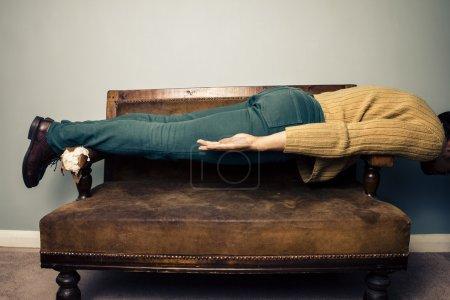 Photo pour Jeune homme en position de planche sur un vieux canapé - image libre de droit