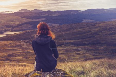 Woman sitting on mountain top and contemplating...